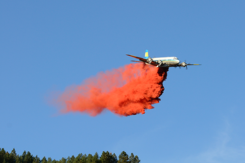 Plane dropping flame retardant chemicals on wildfire